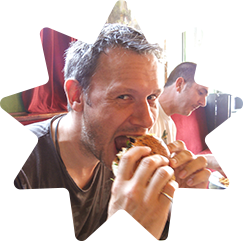 Daniel tucking into a burger that is clearly too big for him