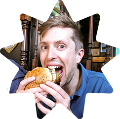 Greg eating a very large burger and looking quite pleased with himself about it