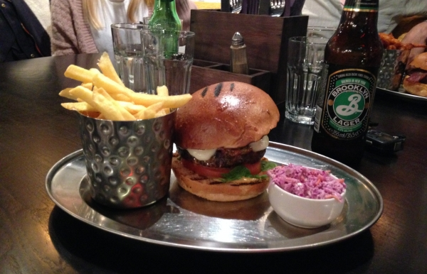 The 'Italian Job' burger coexisting on a silver platter with a portion of tasty fries and tasty slaw