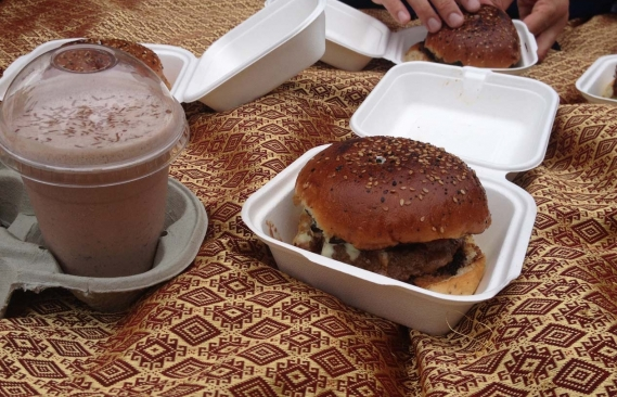 A burger in a foam box with a milkshake next to it
