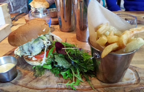 The meal served on wood with chips, a burger, salad and mustard mayo.